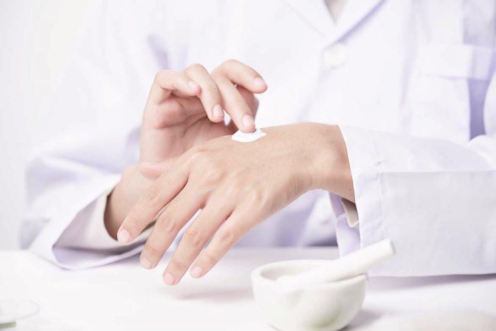врач наносит обезболивающий крем на руки