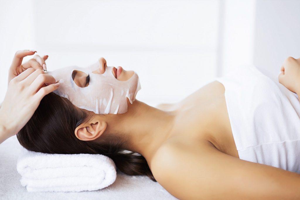 косметолог делает маску девушке