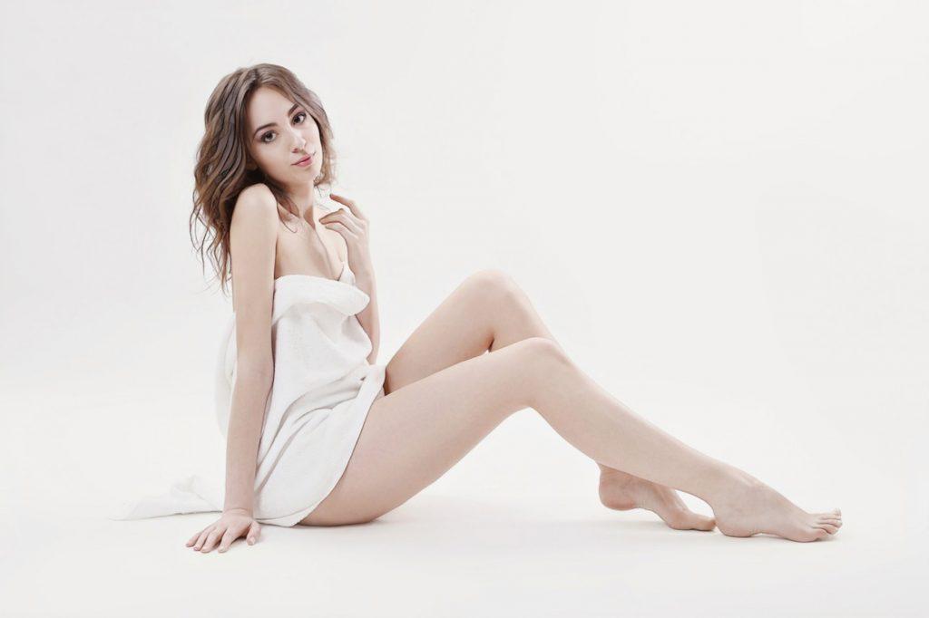 девушка с гладкими ногами, рада избавивщись об боли при эпиляции