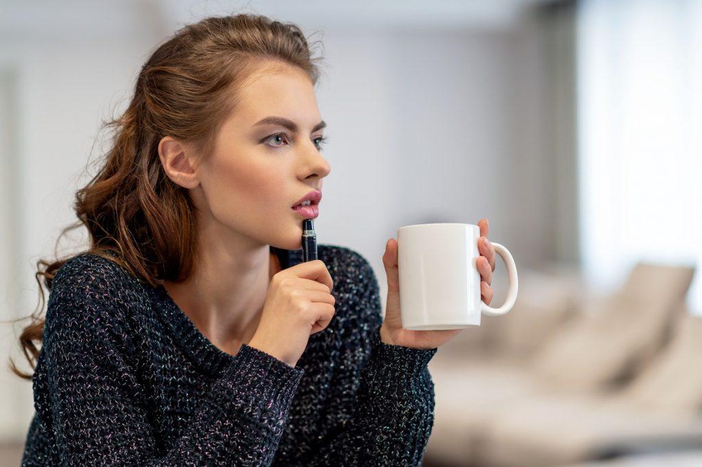 Девушка с чашкой в руках прикладывает к губам ручку