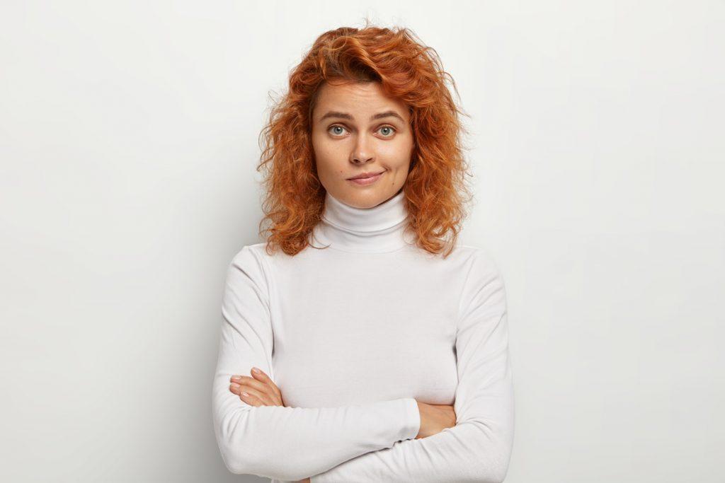 Рыжая девушка с недоверием смотрит