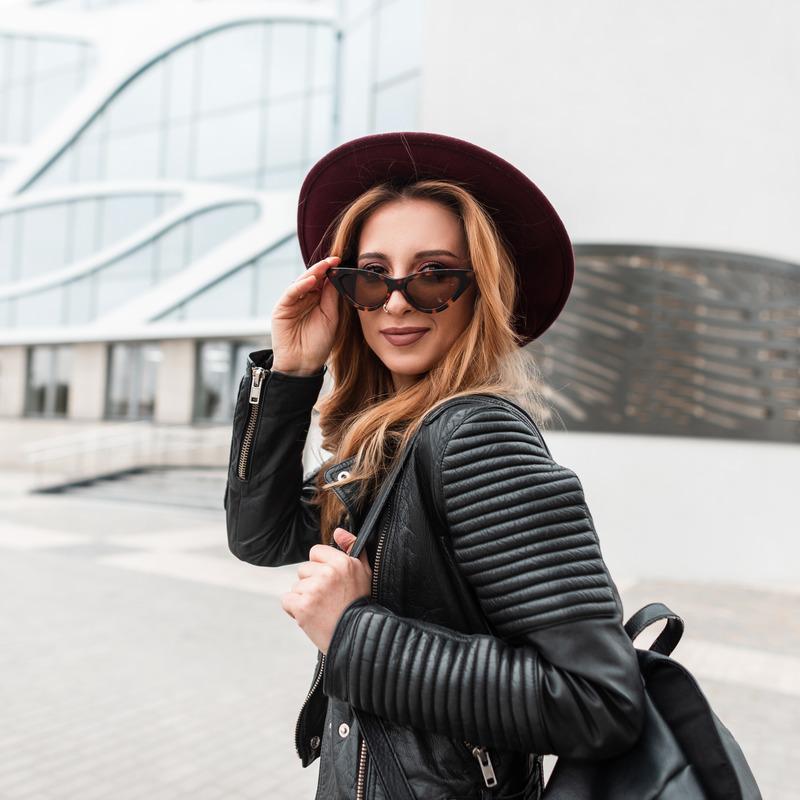 Девушка в кожаной куртке и шляпе гуляет по городу