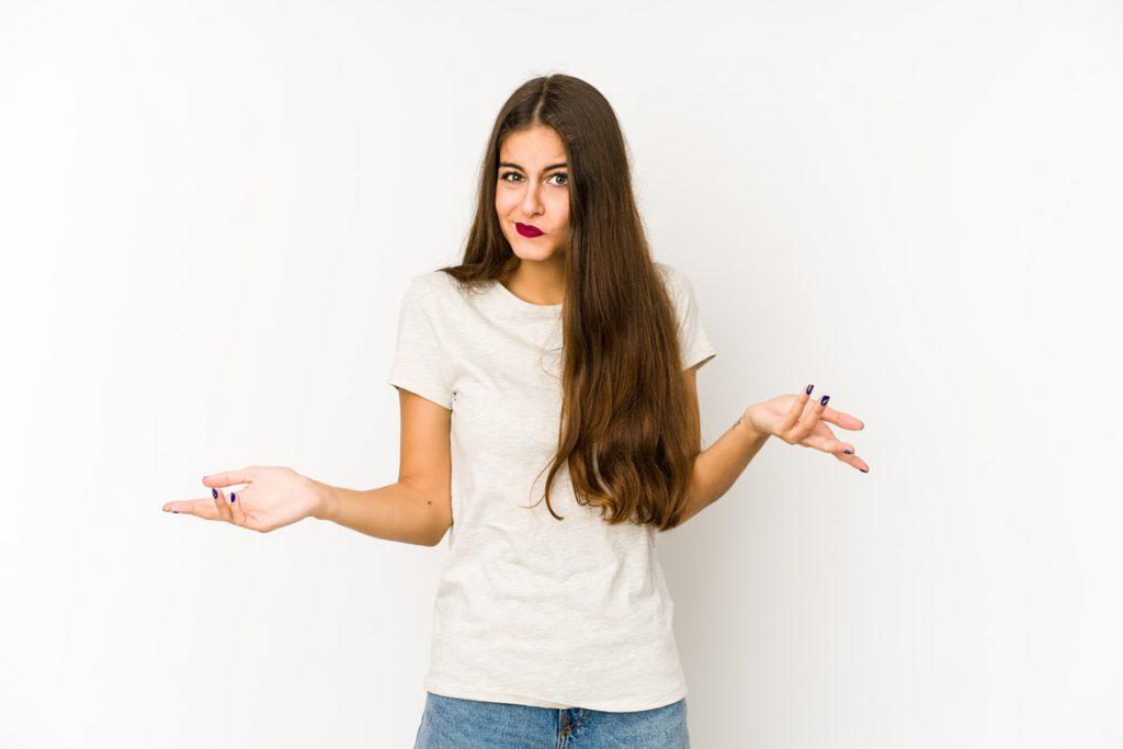 Девушка с длинными волосами разводит руками