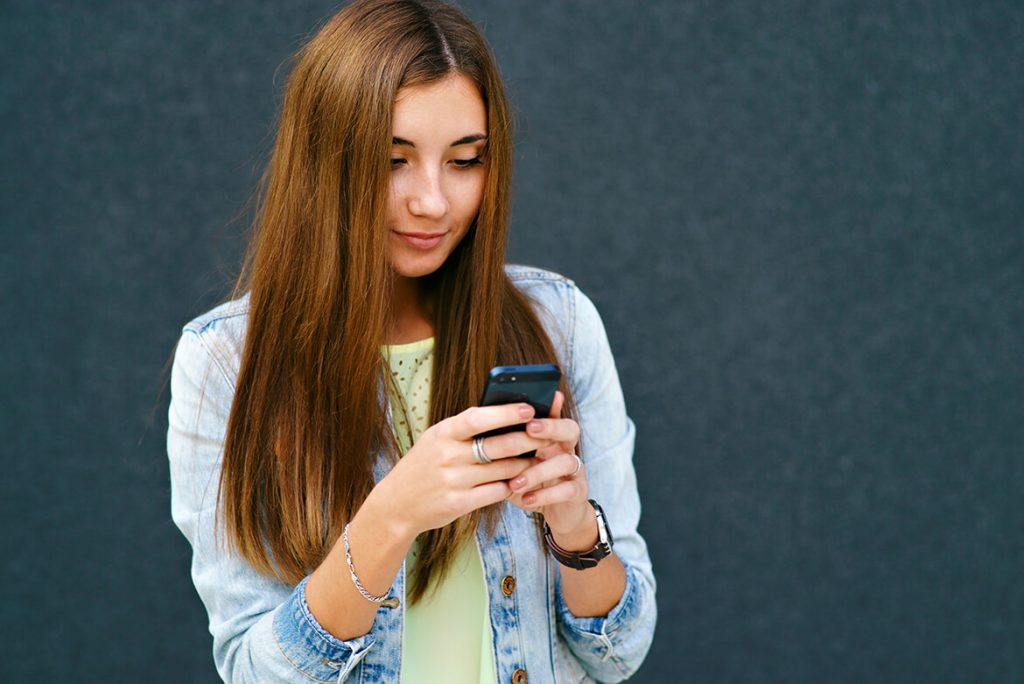Девушка улыбается смотря в телефон