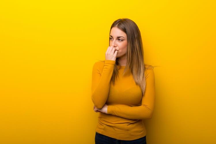 Молодая женщина на желтом фоне сомневается