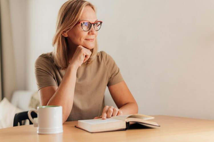 Женщина в очках читает дома