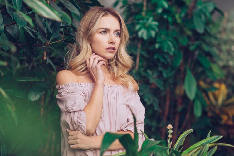 задумчивая блондинка молодая женщина, стоящая в саду, глядя в сторону