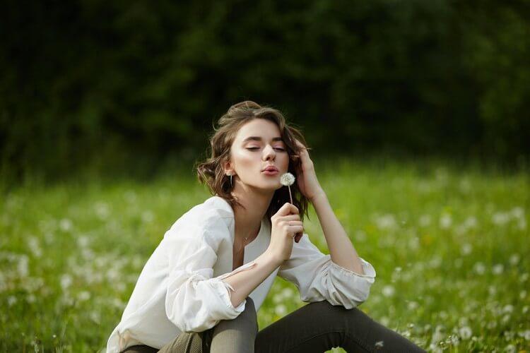 Девушка сидит в поле на весенней траве с цветами одуванчика
