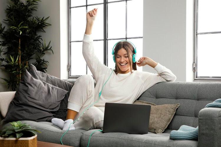 Счастливая девушка сидит дома с ноутбуком