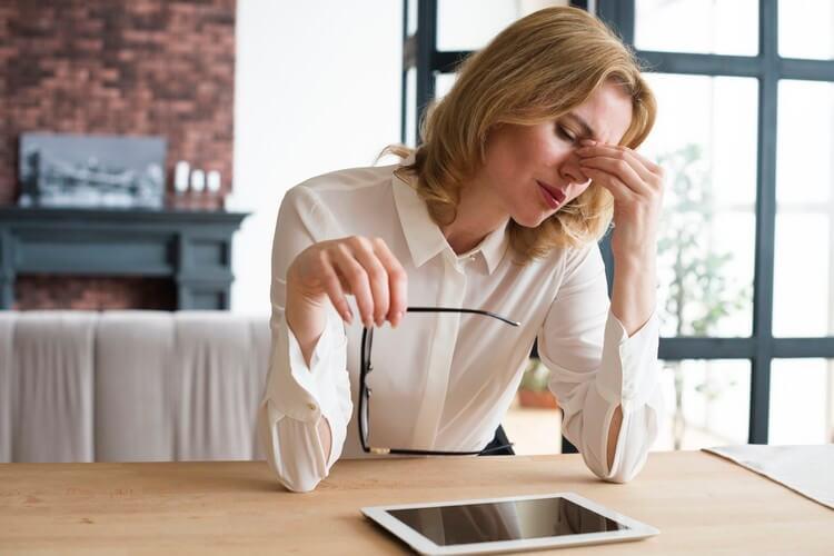Печальная деловая женщина за столом с планшетом