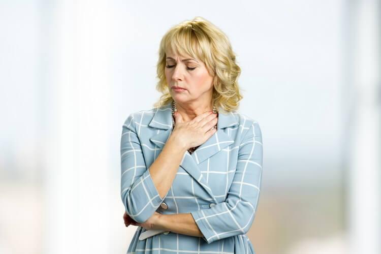 Взрослая женщина держится за горло
