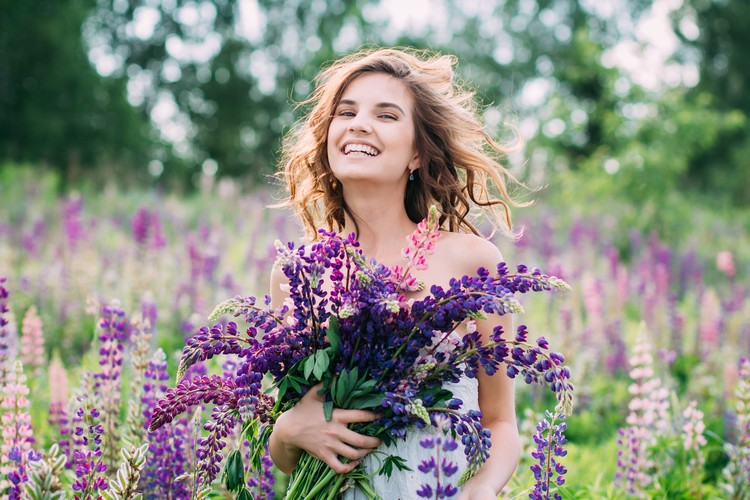 Девушка с букетом люпина на поле
