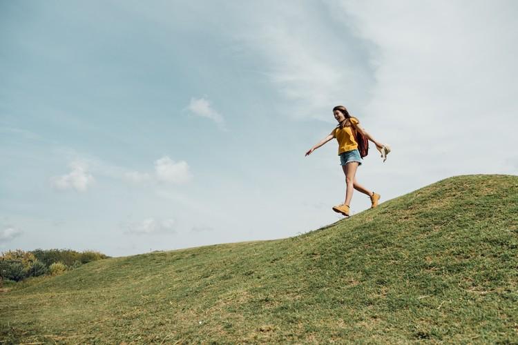 Снимок женщины, спускающейся с холма Premium