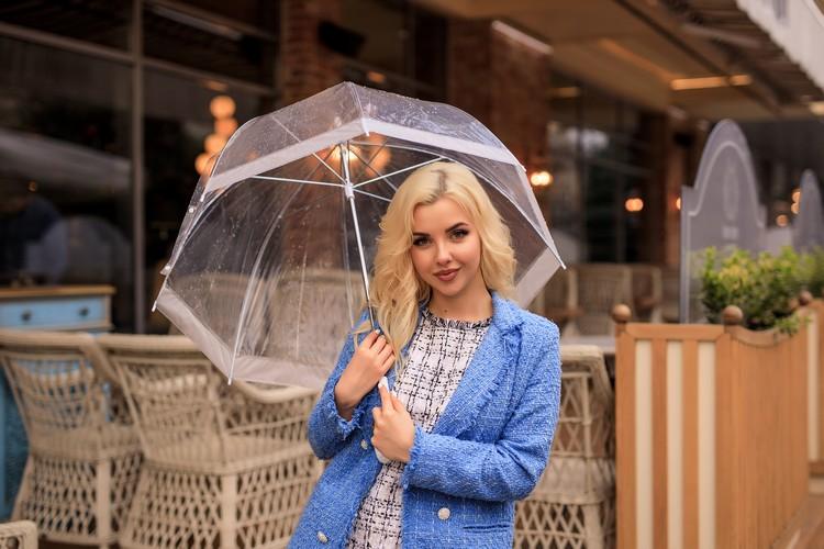 Портрет красивой молодой блондинки, держащей зонт под дождем на городской улице
