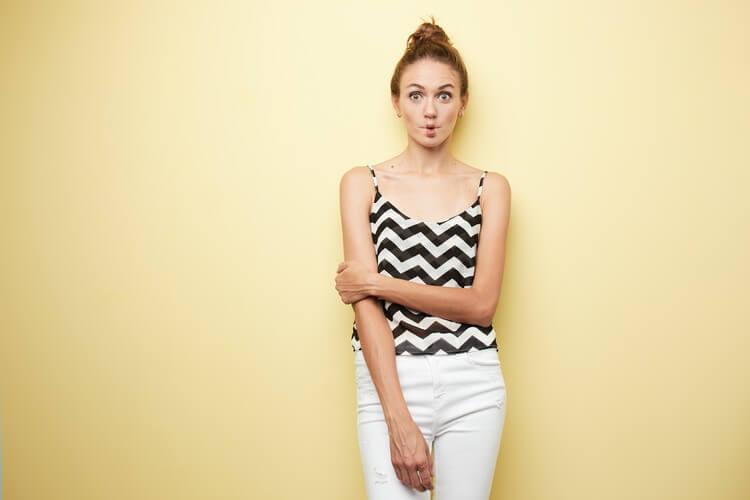 Симпатичная девушка в полосатом топе и белых джинсах скромно стоит на желтом фоне