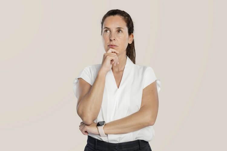 Задумчивая женщина трогает подбородок
