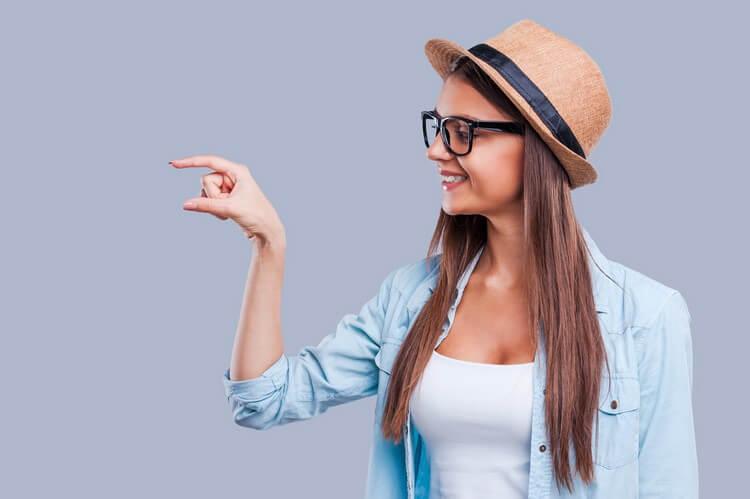 привлекательной молодой женщины, показывающей размер рукой