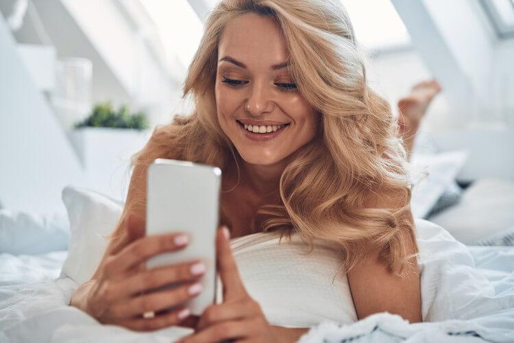 Красивая молодая улыбающаяся женщина с помощью смартфона