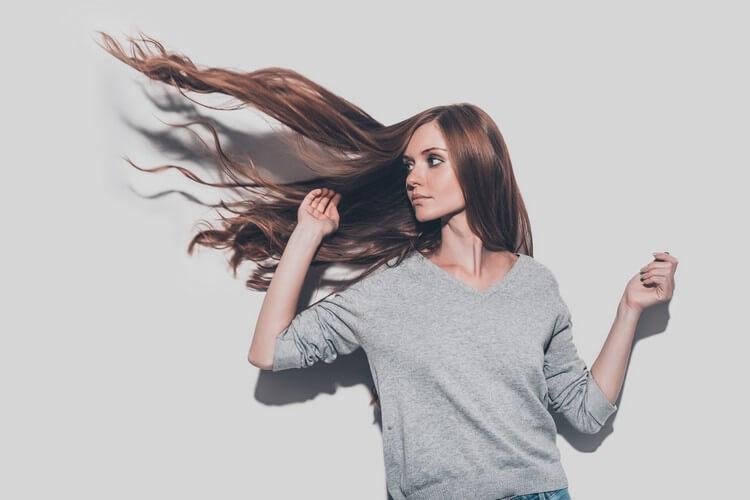 привлекательная молодая женщина с взъерошенными волосами смотрит в сторону,