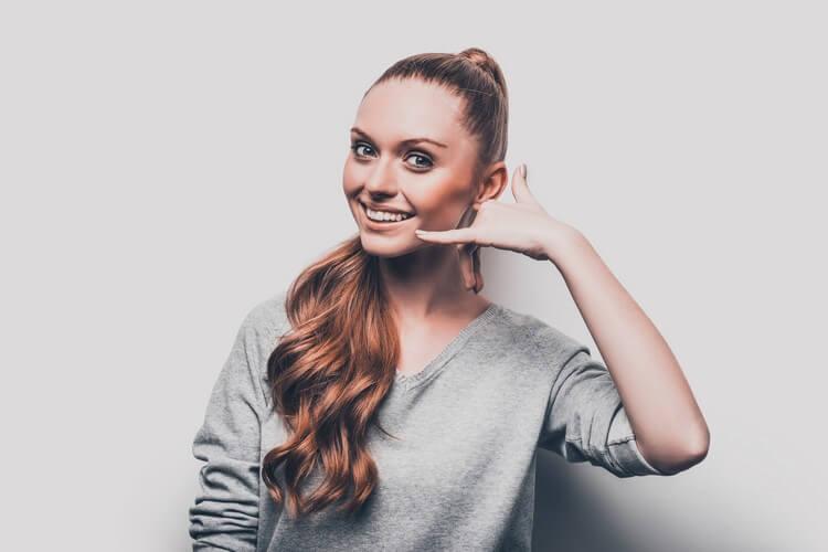 привлекательная молодая женщина жестикулирует по телефону возле лица и улыбается стоя