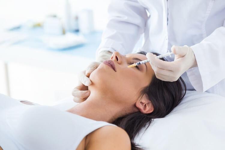 Красивая молодая женщина, получать косметические инъекции Ботокса в ее лице