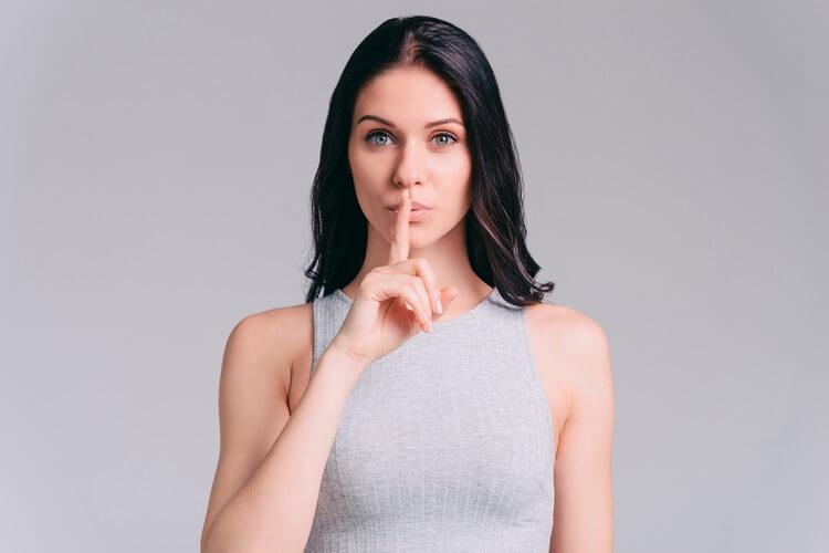 привлекательная молодая женщина, держащая палец на губах стоя