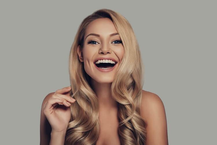 красивая молодая женщина смотрит в камеру и улыбается