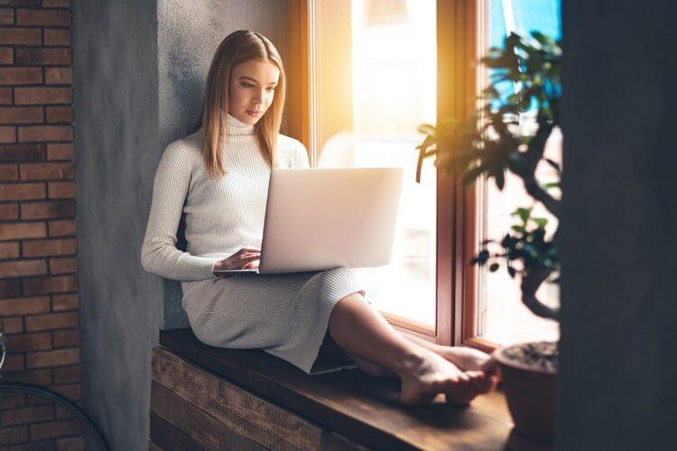 красивая молодая женщина с помощью своего ноутбука, сидя на подоконнике дома