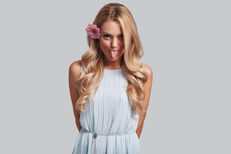 игривая молодая женщина с цветком в волосах